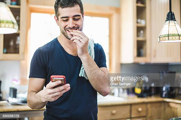 Man eating and using smartphone in kitchen