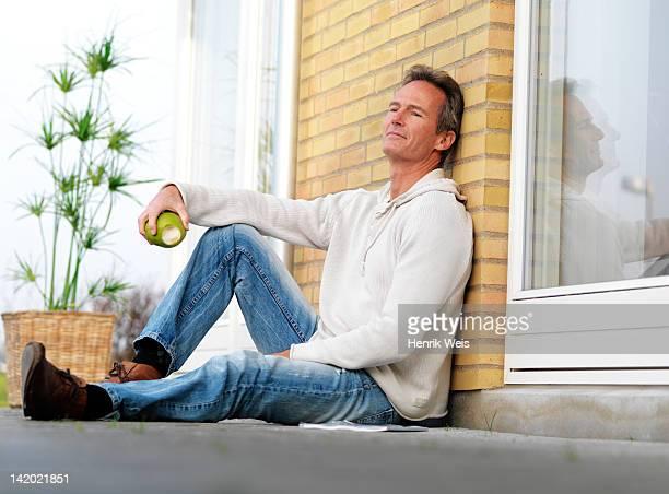 Man eating apple on porch