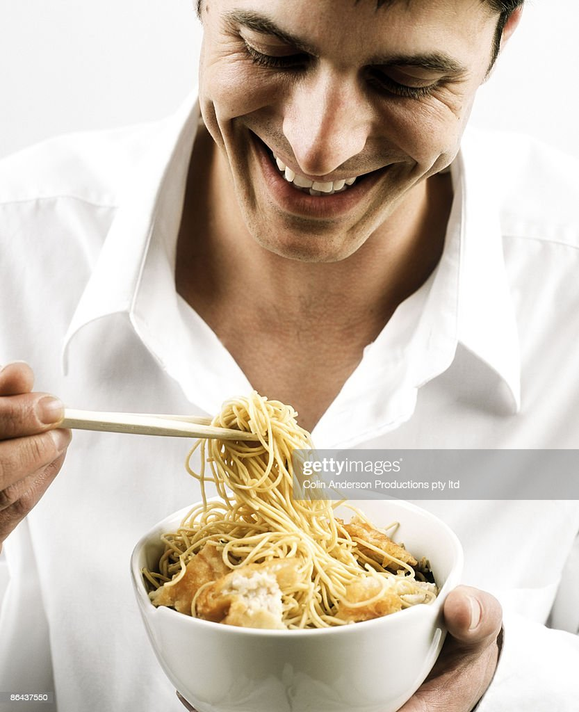 Man eating asian noodles : Stock Photo