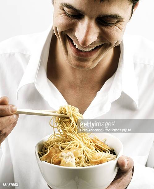 Man eating asian noodles