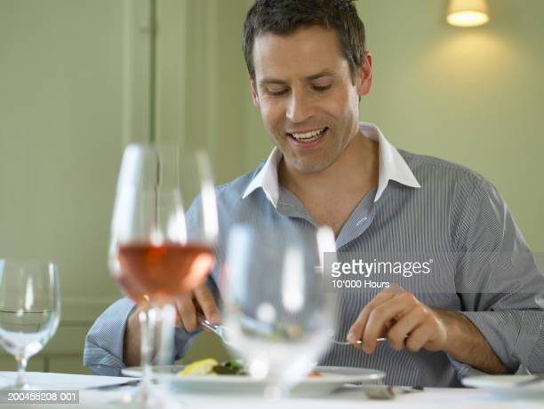 Man eating at table in restaurant