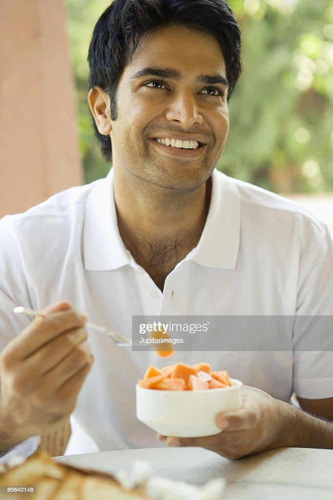 Man eating bowl of fruit : Stock Photo