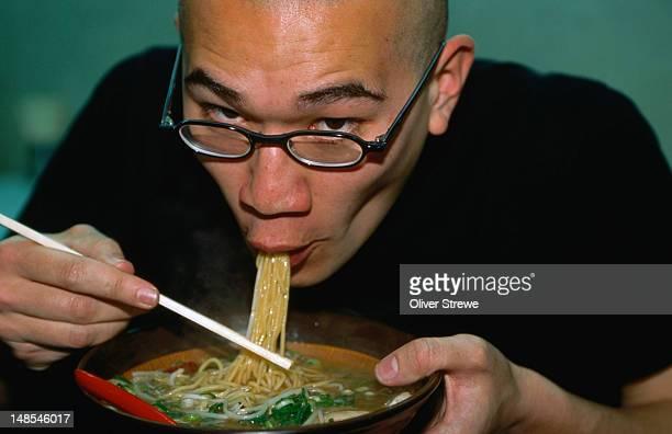 Man eating bowl of miso ramen.