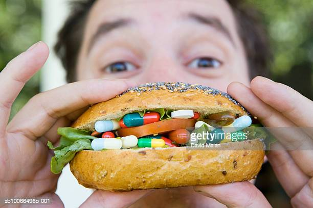 Man eating bread roll filled with medical pills and capsules