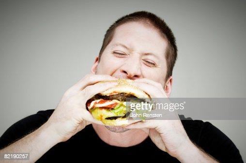man eating burger : Stock Photo