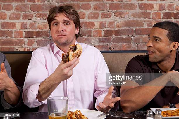 man eating burger with friends