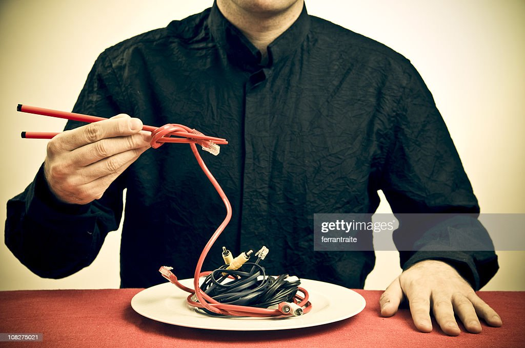 Man Eating Cables with Chopsticks, Toned : Stock Photo