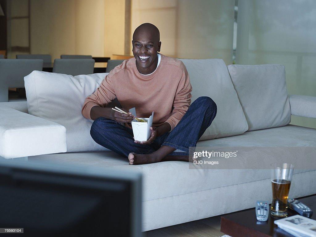 Man eating Chinese food watching television