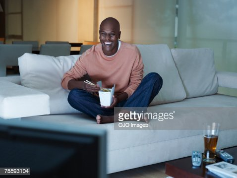 Man eating Chinese food watching television : Stock Photo