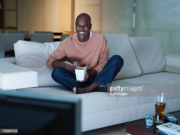 Man eating Chinese food watching television