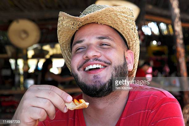 Man eating chips and salsa in beach bar, smiling