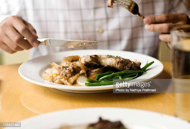 Man eating chops pork and filet mignon