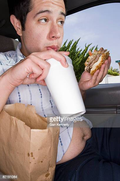 Man eating fast food in his car