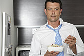 Man eating from container in kitchen
