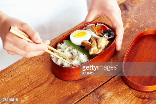 Man eating from lunch box with chopsticks, close-up of hands