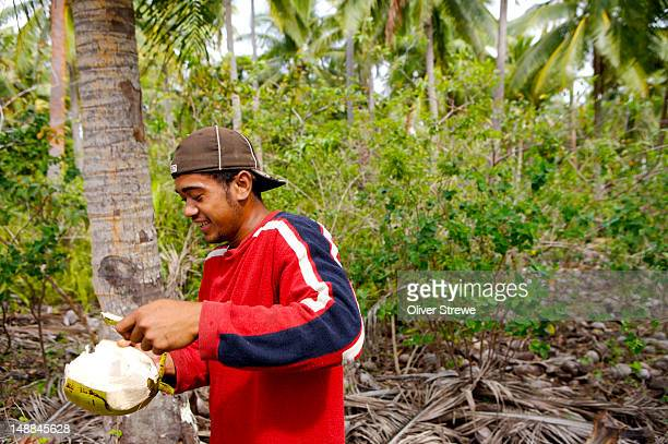 Man eating green coconut, Taianas beach resort.