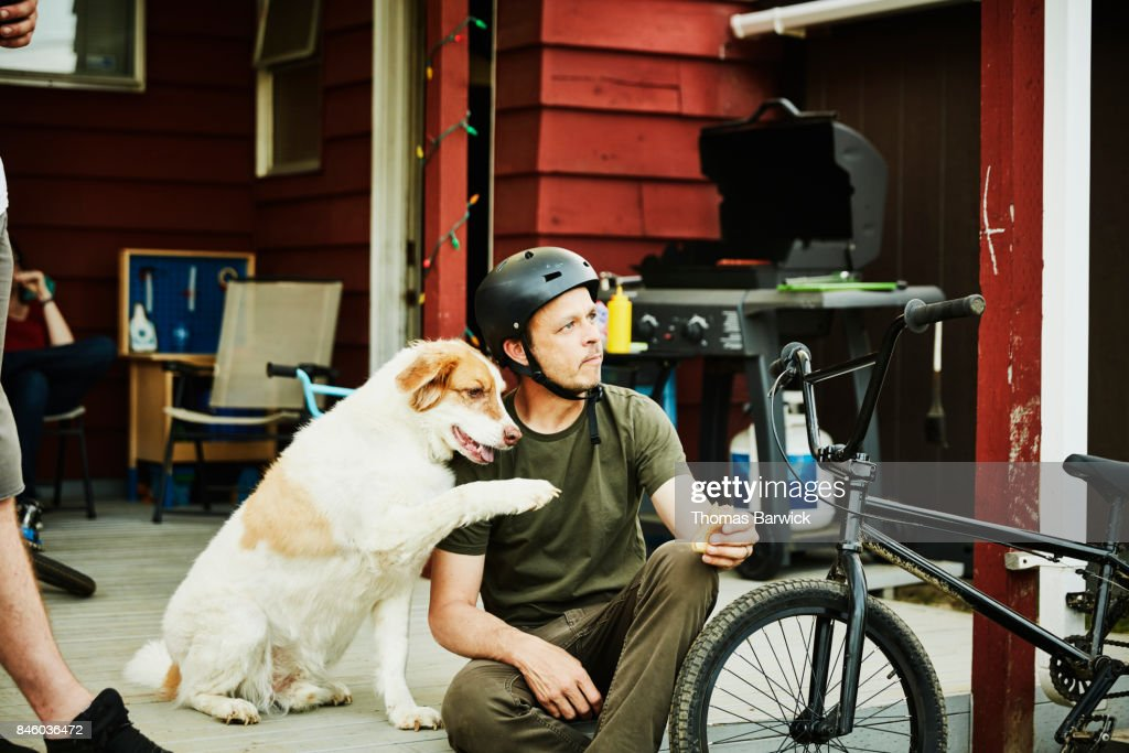 Man eating hot dog while hanging out on back porch with dog : Stock Photo