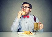 Business man eating junk food drinking beer