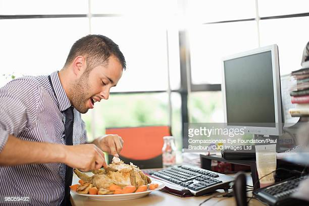 man eating large meal at a desk