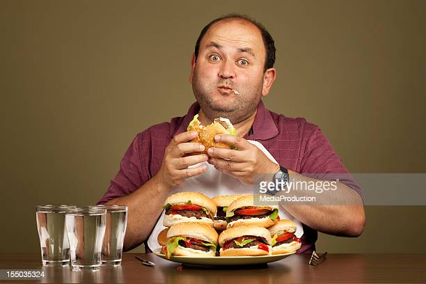 Man eating many burgers