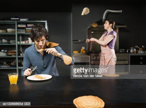 Man eating pancake, while woman turning them in pan : Stock Photo