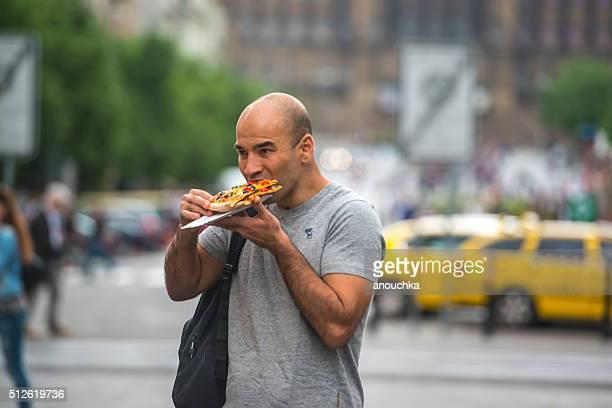 Man eating pizza on Prague street
