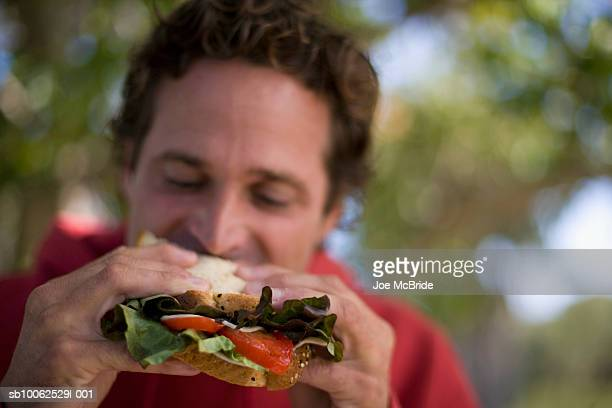 Man eating salad sandwich, outdoors, close-up