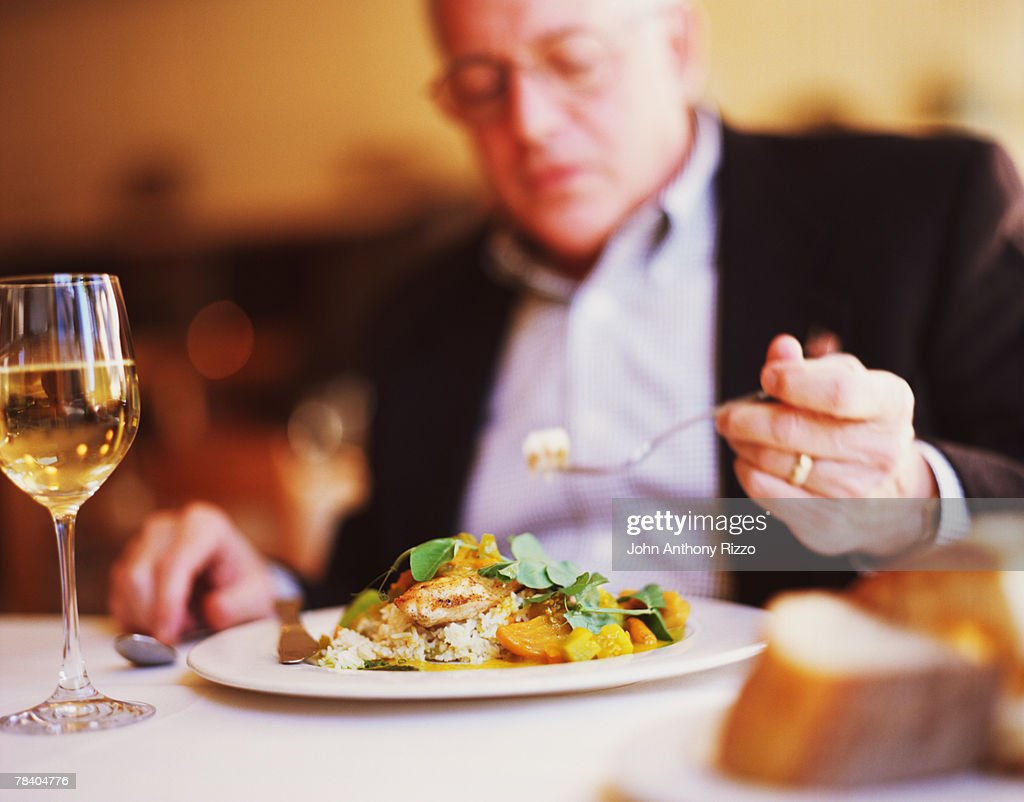 Man eating salad with wine : Stock Photo