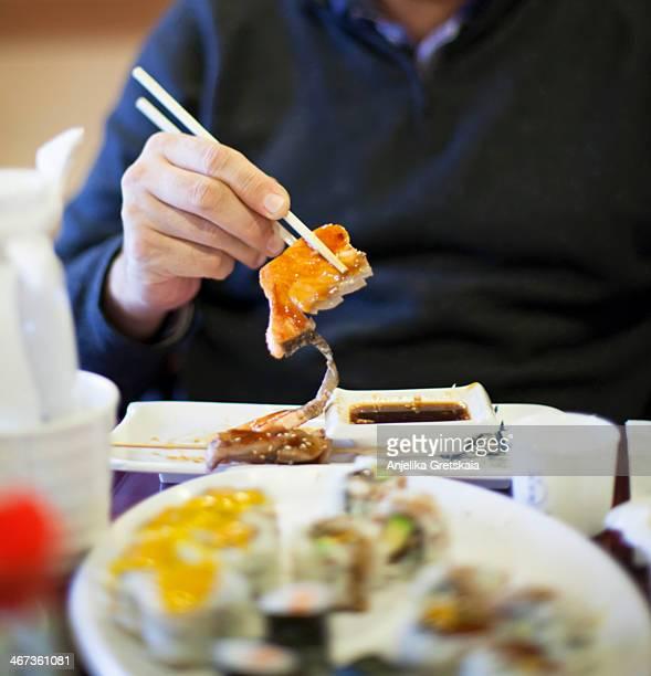 Man eating salmon in teriyaki sauce