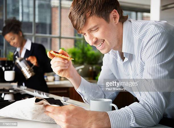 Man eating toast with woman in background pouring coffee