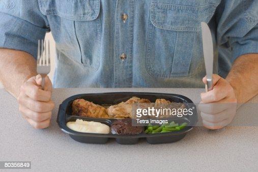 Man eating TV dinner