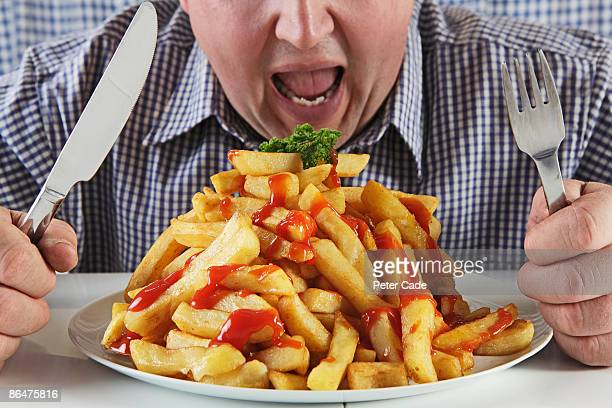 Man eating very large plate of fries