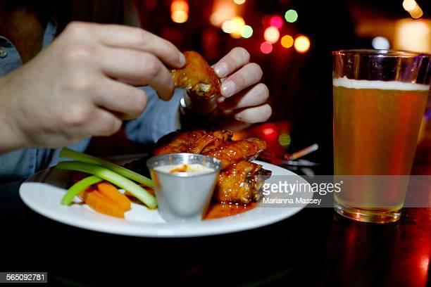 A Man Eating Wings At A Bar