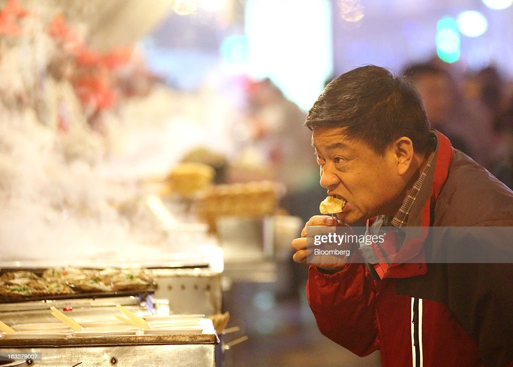 A man eats a dumpling at a stall in a market at night in Beijing, China, on Wednesday, March 6, 2013. China maintained its economic-growth target at 7.5 percent for 2013 while setting a lower inflation goal of 3.5 percent, setting up a challenge for new leaders to keep prices in check without harming expansion. Photographer: Tomohiro Ohsumi/Bloomberg via Getty Images
