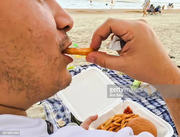 St Augustine Florida December 29 2014 A man eats a French fry while enjoying a Christmas barbecue meal on St Augustine beach