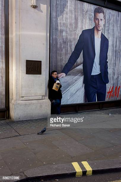 A man eats a sandwich beneath a poster for retailer HM on Oxford Street It is lunchtime on a winter's afternoon and the man has stopped to rest...
