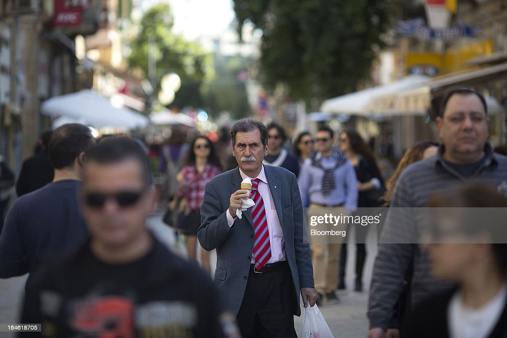 A man eats an icecream as he walks along a busy street in Nicosia, Cyprus, on Monday, March 25, 2013. In a replay of tensions over aid for Greece at the outset of the crisis, European governments had wrangled over aid for Cyprus for nine months, exposing holes in the revamped economic management system that was built in three years of emergency policymaking, often at all-night summits. Photographer: Photographer: Simon Dawson/Bloomberg via Getty Images