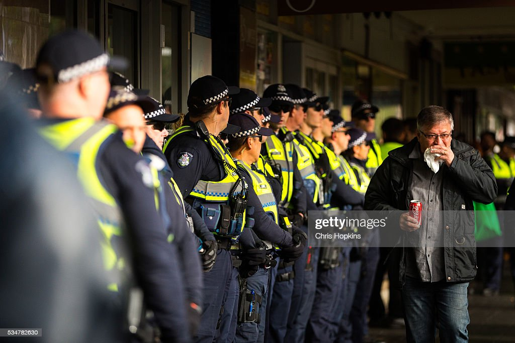 A man eats as he walks past an increased police presence on May 28, 2016 in Melbourne, Australia in response to violent anti-racism rallies. Violence erupted when participants in a 'Say No To Racism' rally protesting the forced closure of Aboriginal communities, off-shore detention centres and Islamophobia met with a counter 'Anti-Islam' rally organised by the True Blue Crew and backed by the United Patriots Front.