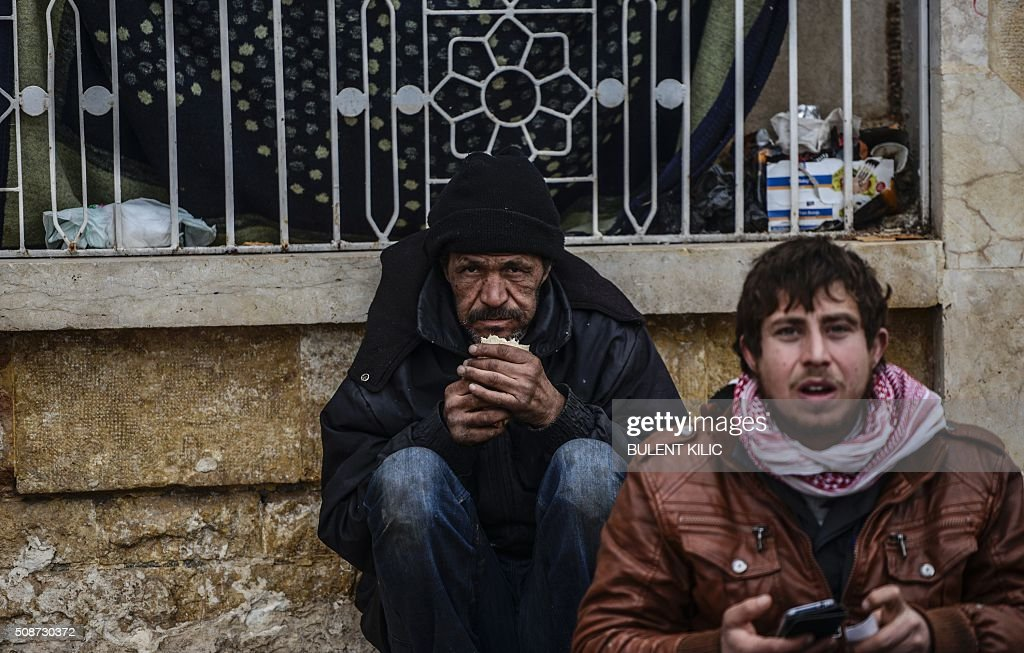A man eats food as Syrians fleeing the northern embattled city of Aleppo wait on February 6, 2016 in Bab Al-Salam, near the city of Azaz, northern Syria, near the Turkish border crossing. Thousands of Syrians were braving cold and rain at the Turkish border Saturday after fleeing a Russian-backed regime offensive on Aleppo that threatens a fresh humanitarian disaster in the country's second city. Around 40,000 civilians have fled their homes over the regime offensive, according to the Syrian Observatory for Human Rights monitor. / AFP / BULENT KILIC