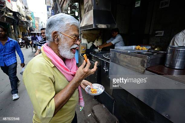 A man eats jalebi at the old famous Jalebi wala at the corner of Dariba in Chandni Chowk on August 20 2014 in New Delhi India Chandni Chowk often...