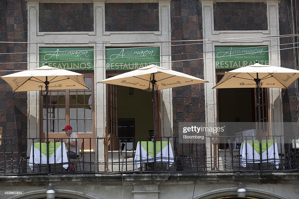 A man eats lunch on the balcony of a restaurant near the traditional main plaza known as the Zocalo in Mexico City, Mexico, on Thursday, Aug. 21, 2014. Mexican consumer prices rose more than analysts expected in the first half of August and the unemployment rate rose to 5.47 percent in July compared with 4.8 percent in June. Photographer: Susana Gonzalez/Bloomberg via Getty Images