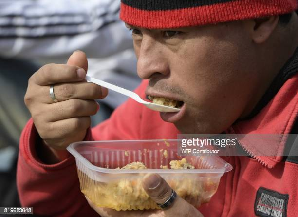 A man eats stew during a protest by activists from social organizations against the economy policy of Argentina's President Mauricio Macri at Plaza...