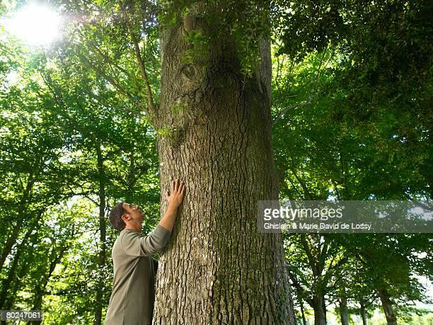 Man embracing a tree trunk.