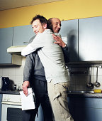 Man embracing boss in kitchen