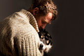 man embracing dog,studio shot