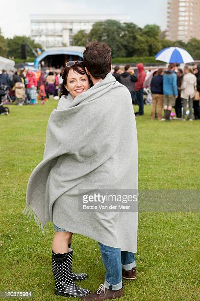 Man embracing girlfriend with blanket at festival.