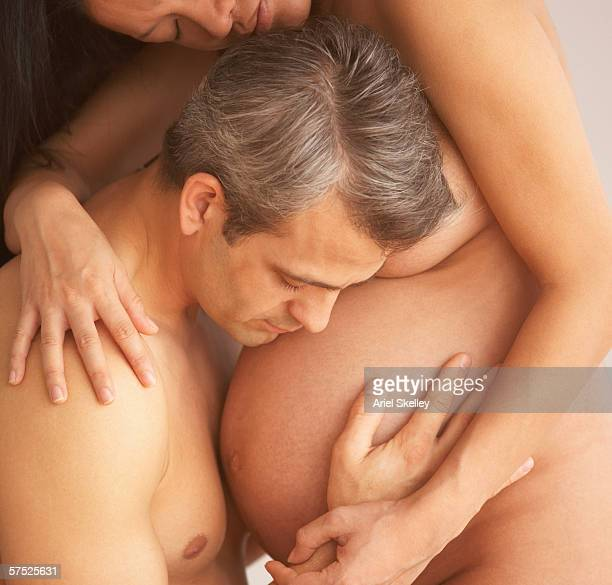 Man embracing his nude pregnant wife