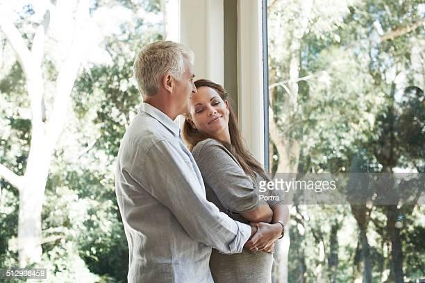 Man embracing woman by glass window