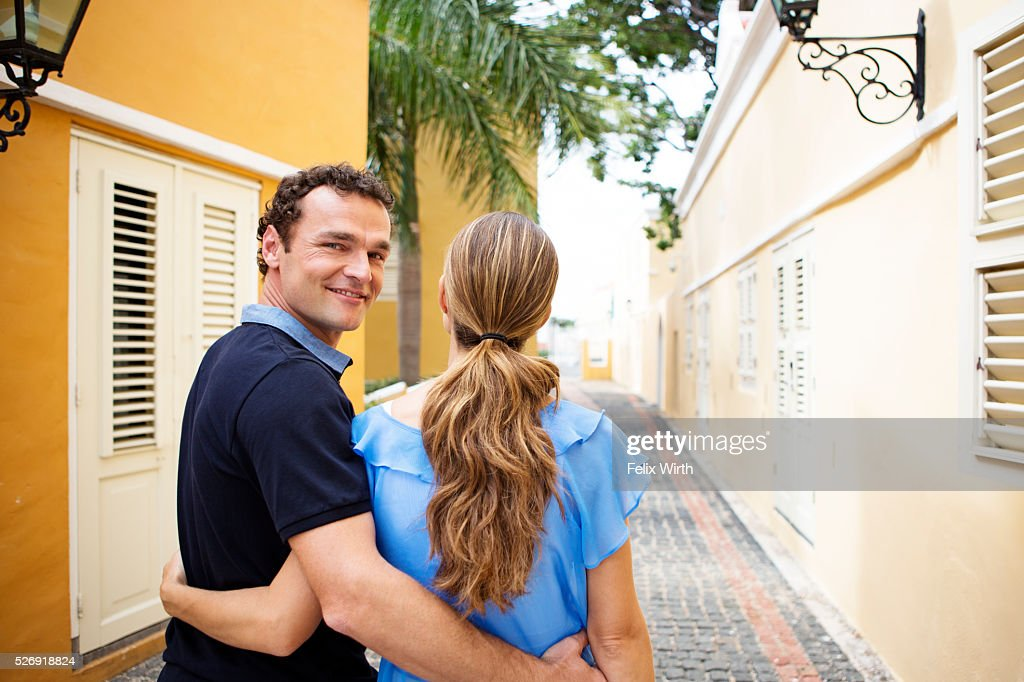 Man embracing woman on narrow street : Stock-Foto