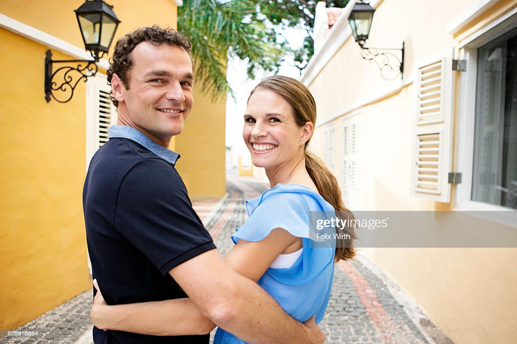 Man embracing woman on narrow street : Stock Photo